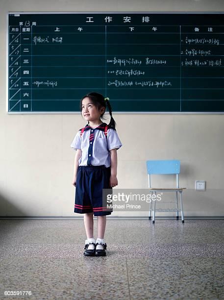 Student Standing in Front of Blackboard