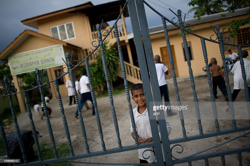 A student stands inside the main gate of the Iqro Al-Quran Bestari Academy for the orphanage in the suburbs of Kuala Lumpur on November 7, 2012.