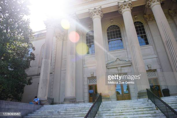 Student studies outside the closed Wilson Library on the campus of the University of North Carolina at Chapel Hill on August 18, 2020 in Chapel Hill,...