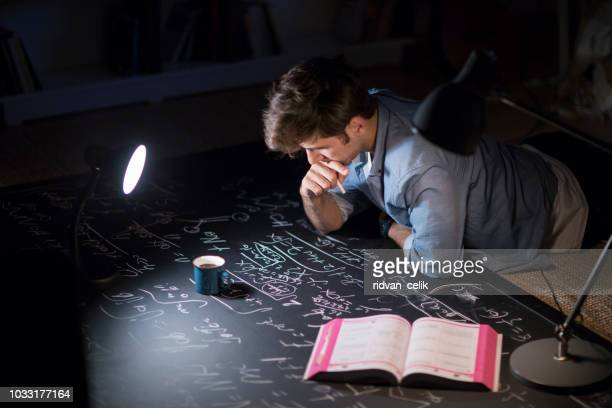 student studying at night with a desk lamp on - excesso imagens e fotografias de stock