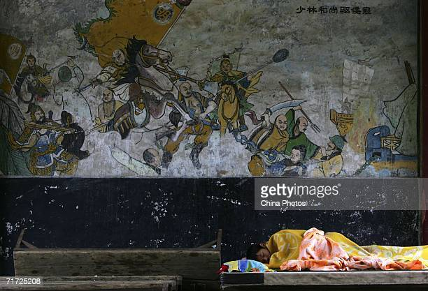 A student takes a nap in front of fresco showing monks driving Japanese invaders away at the Tagou Martial Arts School near the Shaolin Temple on...