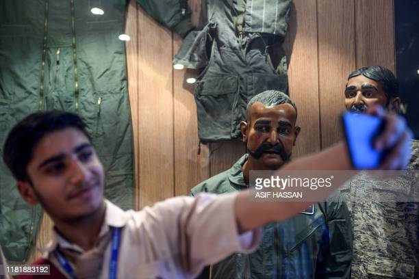 A student takes a selfie in front of the statue of Indian pilot Wing Commander Abhinandan Varthaman whose plane was shot down over Kashmir earlier...