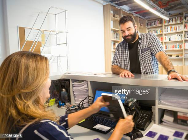 student taking a book on a library. - borrowing stock pictures, royalty-free photos & images