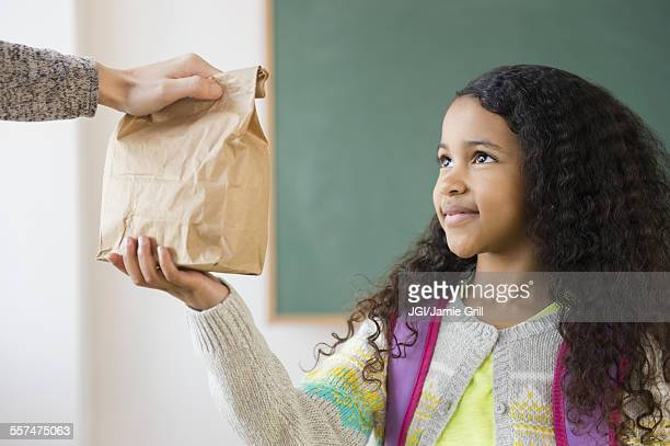 Student taking brown bag lunch in classroom