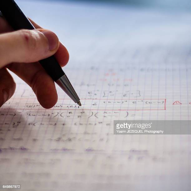 Student taking notes in mathematical classroom