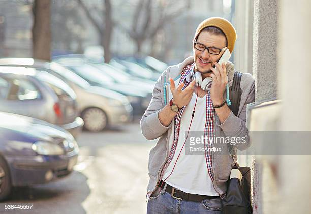 student talking on the phone - hoodie headphones stock pictures, royalty-free photos & images