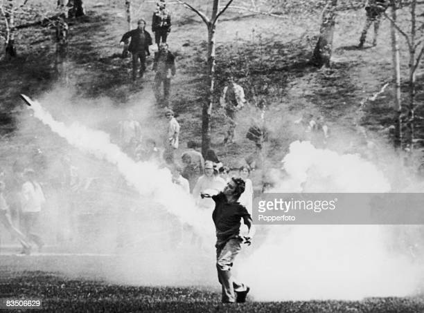 Student throws a tear gas canister back at National Guardsmen during a demonstration against the American invasion of Cambodia, at Kent State...