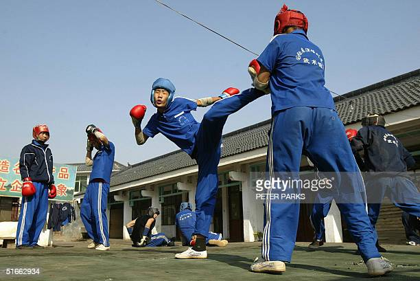 A student training in the art of Xingyi Quan kicks his opponant at the famed Shaolin Monestary in Henan province in central China 03 November 2004...