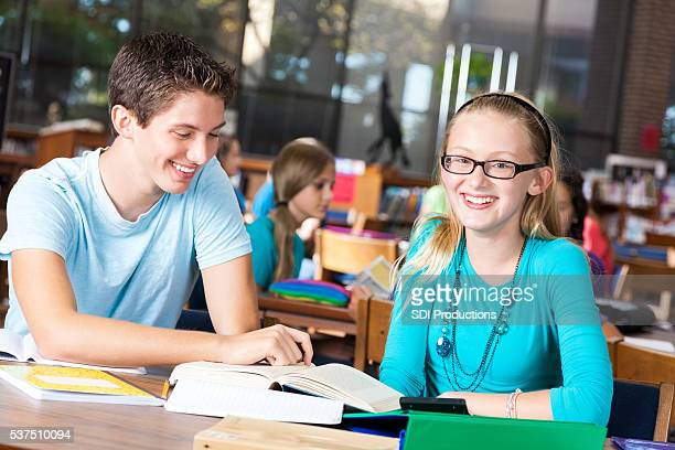 Student tutors girl in library
