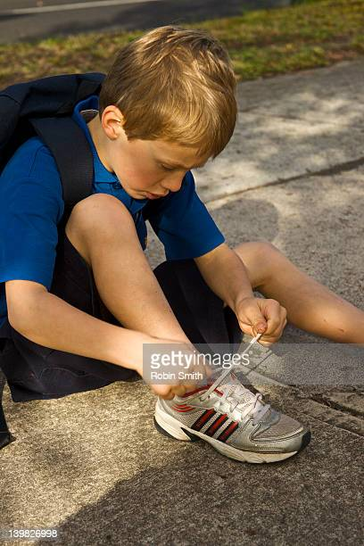 student tying his shoes