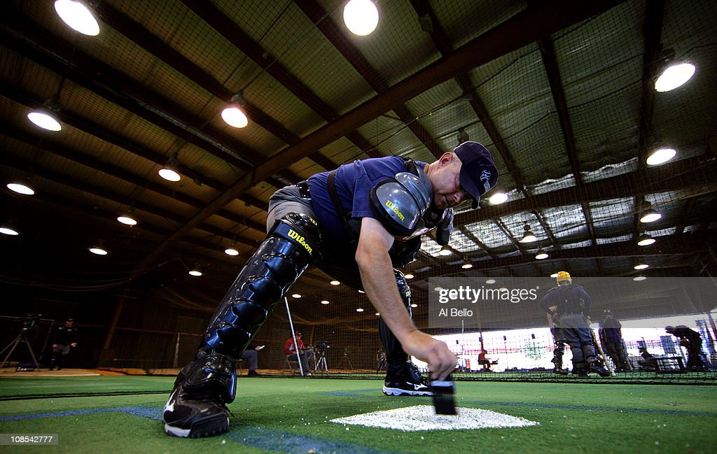 A student umpire wipes off home plate before calling balls and strikes in a simulated game while under the watch of an instructor who is playing the role of a team manager at the indoor batting cages during the Jim Evans Academy of Professional Umpiring on January 28, 2011 at the Houston Astros Spring Training Complex in Kissimmee, Florida. Jim Evans was a Major League Umpire for 28 years that included umpiring four World Series. Many of his students have gone on to work on all levels of baseball including the Major Leagues.