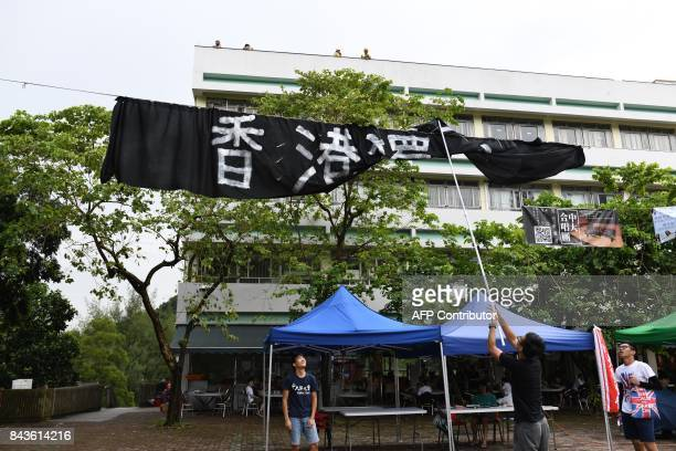 Student union members untangle a proHong Kong independence banner after a heavy downpour at the Chinese University of Hong Kong in Hong Kong on...
