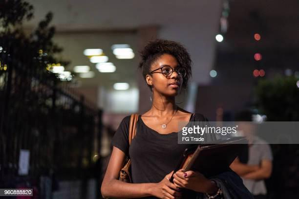 student university walking in the street at night - academy stock pictures, royalty-free photos & images