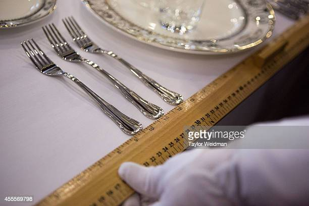 A student uses a ruler to measure the distance between forks before a formal dinner at The International Butler Academy China on September 16 2014 in...