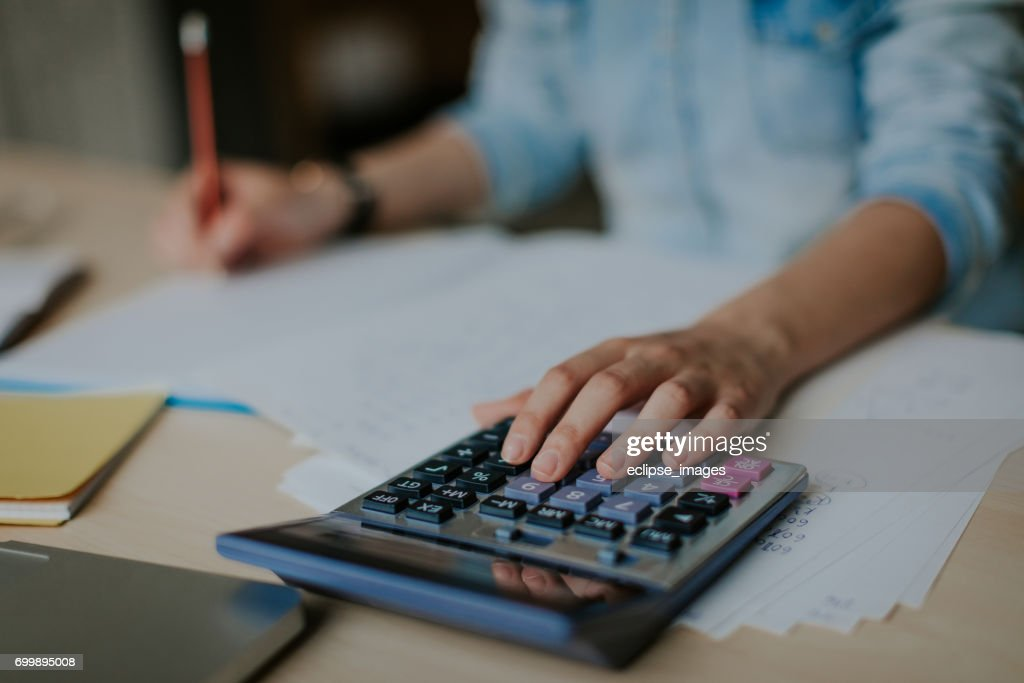 Student uses calculator to help with math homework : Stock Photo