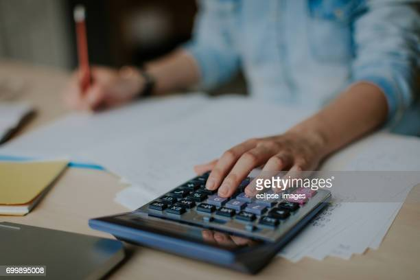 student uses calculator to help with math homework - calculator stock photos and pictures