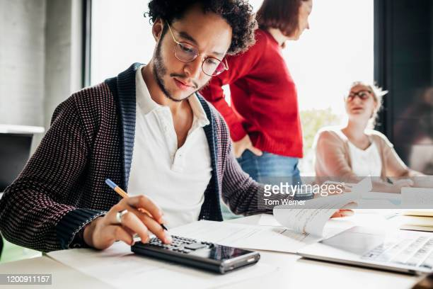 student using calculator to work out math problem - campus stock pictures, royalty-free photos & images