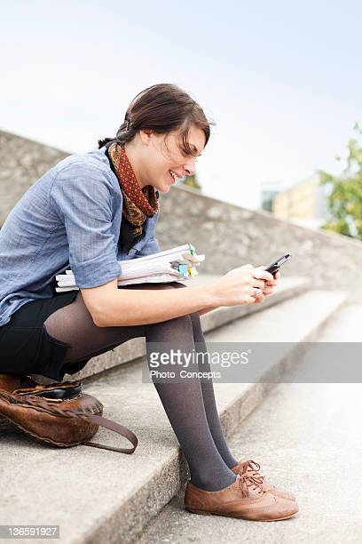 student using cell phone on steps - peterborough ontario stock photos and pictures