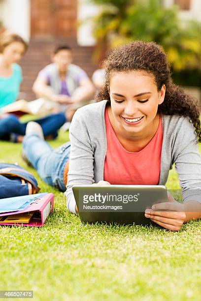 Student Using Digital Tablet While Lying On Campus