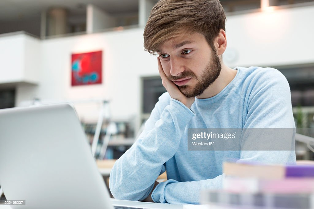 Student using laptop in a university library : Stock Photo