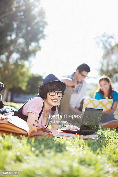 Student using laptop in grass outdoors