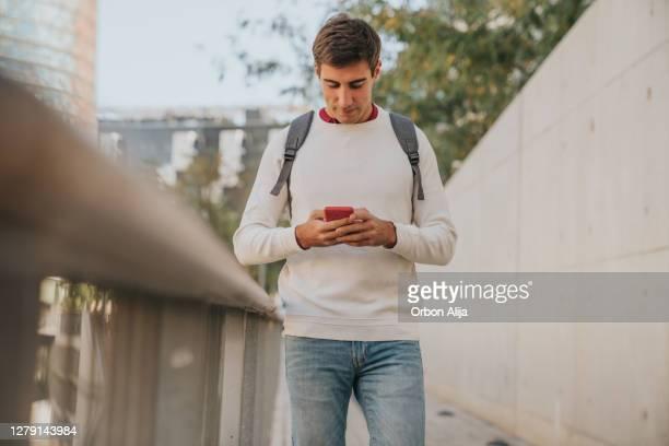 スマートフォンを使った学生 - 若い男性だけ ストックフォトと画像