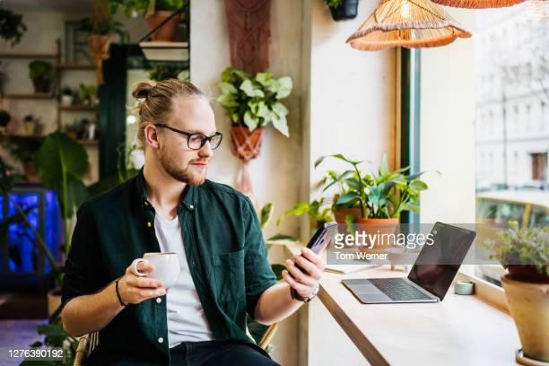 student using smartphone while drinking coffee - フリーランス ストックフォトと画像