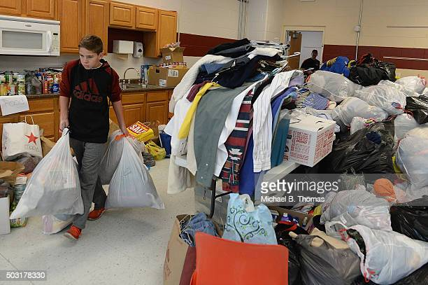 A student volunteer carries donated goods at a flood relief donation drive at Fox High School on January 2 2016 in Arnold Missouri After the record...