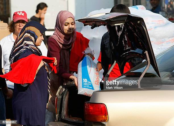A student volunteer hands out ice and packaged meals at a distribution point at the University of Houston September 19 2008 in Houston Texas Parts of...