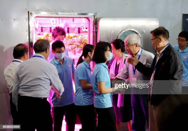 Student volunteers shake hands with scientists after leaving the Lunar Palace 1 a laboratory simulating a lunarlike environment in Beijing on May 15...