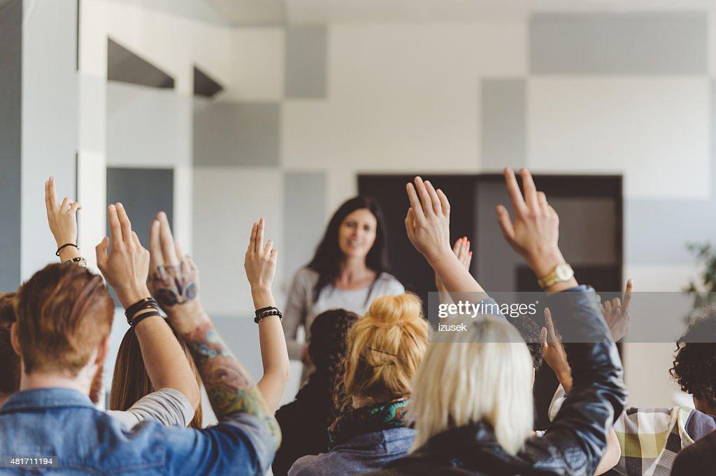Student voting on seminar, raising hands : Stock Photo