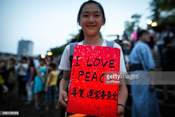 A student wait to float candle lit lanterns with written message quotI LOVE PEACEquot on the Motoyasu River during the 71st anniversary activities...