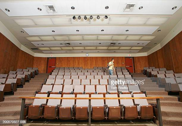 Student walking in empty classroom auditorium