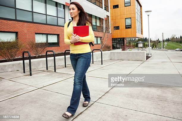 student walking on campus with books - community college stock pictures, royalty-free photos & images