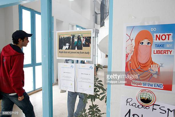 student walking past a poster defending the wearing of niqab (islamic clothing for women) at el manar university, tunis - nikab stock pictures, royalty-free photos & images