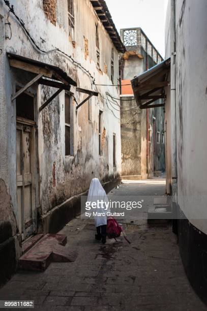 a student walking to school, zanzibar, tanzania - zanzibar island stock photos and pictures