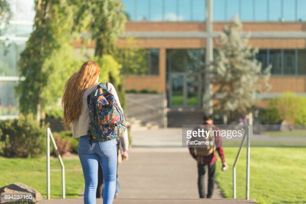 Student walks across campus on the way to her next morning class