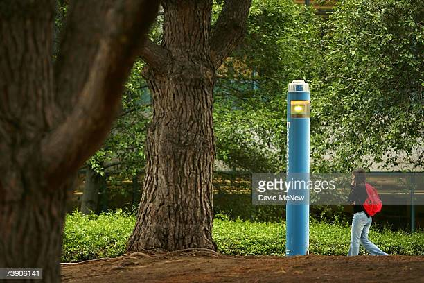 A student walks by an emergency station at the memorial grove of seven pine trees that honors seven people killed by a gunman July 12 1976 inside the...
