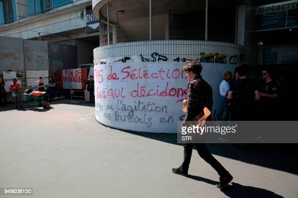 A student walks in front of a banner reading 'No selection our decision' at the entrance of SaintDenis university north of Paris on April 19 2018...