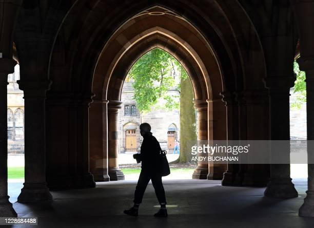 Student walks in the campus of Glasgow university complex, Glasgow, Scotland on September 24, 2020. - An outbreak of Covid-19 has led to 124 students...