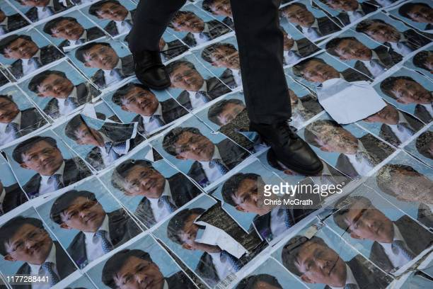 Student walks over posters of pro-China lawmaker Junius Ho during a protest forming a human chain outside the Queen Elizabeth Stadium where Carrie...