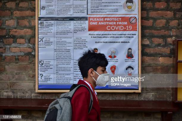 Student walks past a poster of Covid-19 precautions inside the school premises as the schools reopened after one year of break due to the coronavirus...