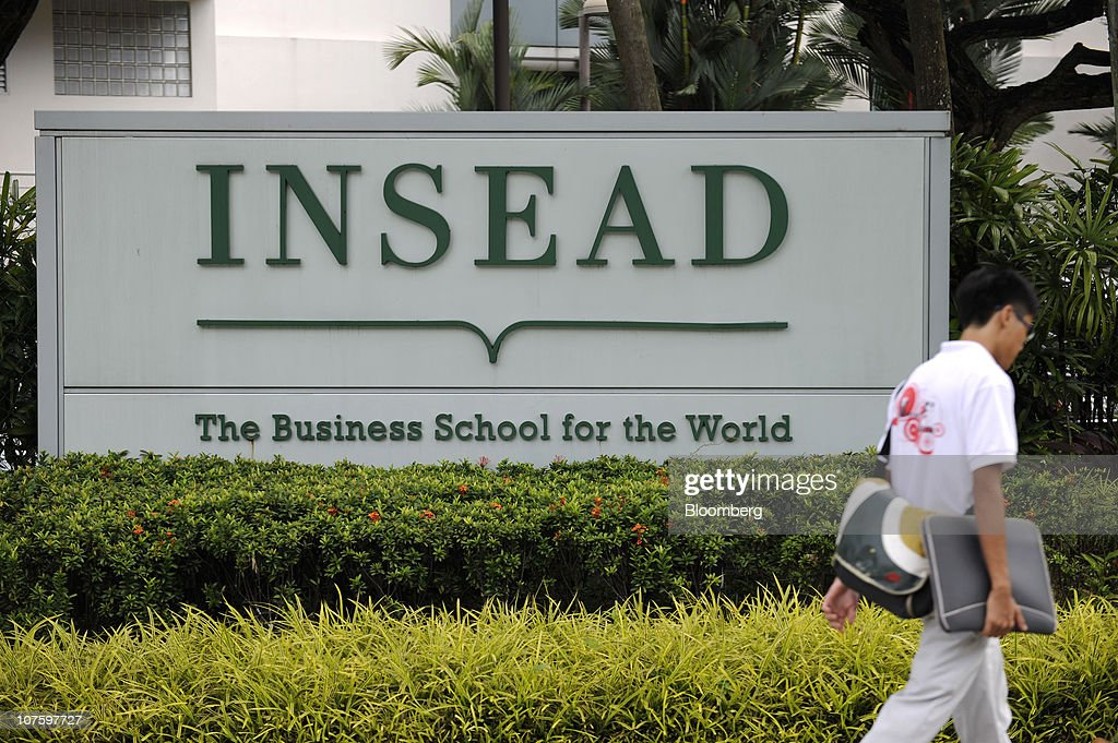 A student walks past a sign for the Asia campus of Insead in Singapore, on Monday, Dec. 6, 2010. Yale University may join Duke University, the University of Chicago, Imperial College London and France's Insead among colleges to set up a campus in Singapore, a nation of 5 million people with a land mass smaller than New York City. The city-state wants to attract 150,000 international students by 2015 as it seeks to boost the contribution education makes to gross domestic product to 5 percent from 3.2 percent last year and 1.9 percent in 2000. Photographer: Munshi Ahmed/Bloomberg via Getty Images