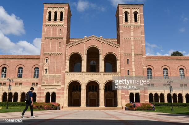 Student walks toward Royce Hall on the campus of University of California at Los Angeles in Los Angeles, California on March 11, 2020. - Starting...