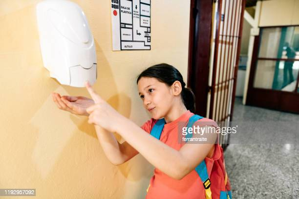student washing hands with hand sanitizer in school - hand sanitizer stock pictures, royalty-free photos & images