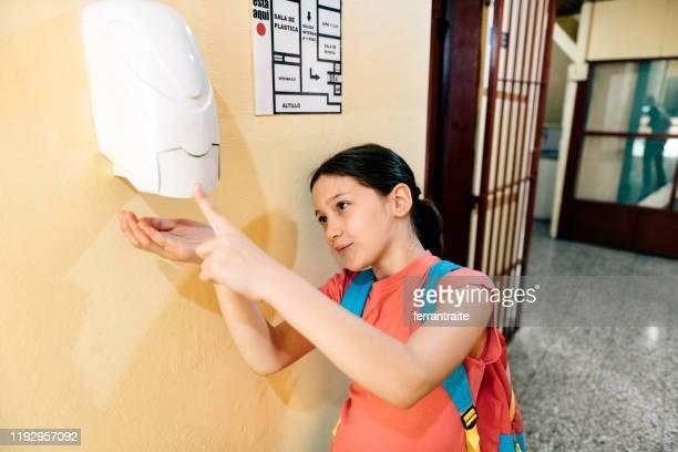estudiante que se lava las manos con desinfectante de manos en la escuela - hand sanitizer fotografías e imágenes de stock