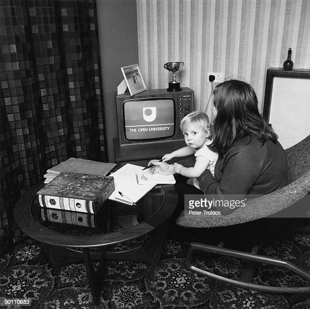 A student watching an Open University broadcast on TV with her child on her lap 9th February 1971 A distance learning university the Open University...