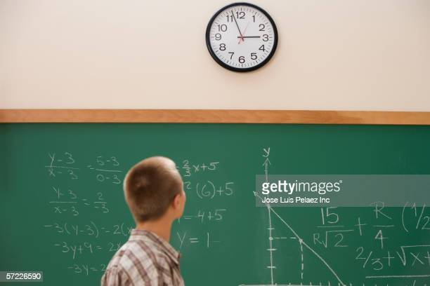 student watching the clock in class - wall clock stock photos and pictures