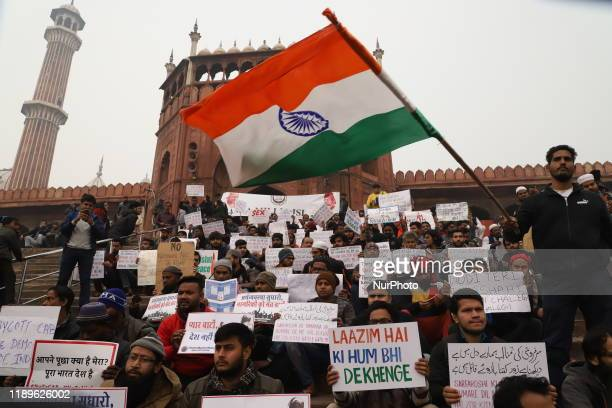A student waves Indian flag during a sit in protest against the Citizenship Amendment Act on the stairs of Jama Masjid in Old Delhi India on 19...