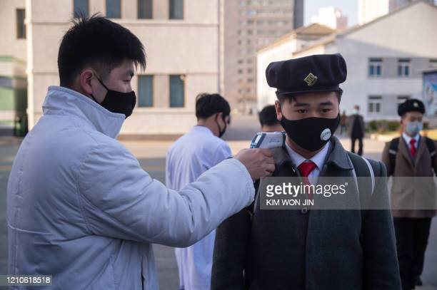 A student wearing a face mask undergoes a temperature check as he arrives for a lecture on preventative measures against the COVID19 novel...